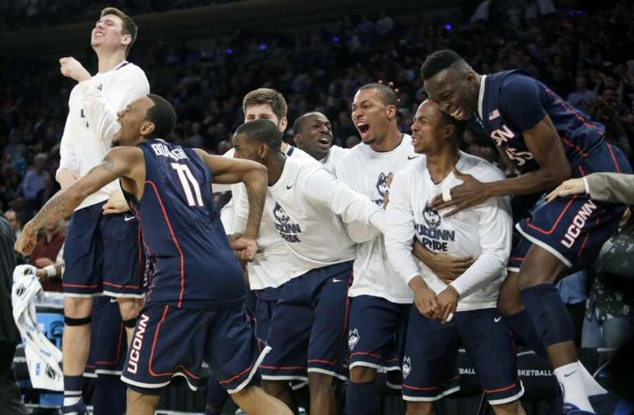 Connecticut's Ryan Boatright (11) leads the cheers on the bench as the Huskies celebrate their victory over Michigan State.