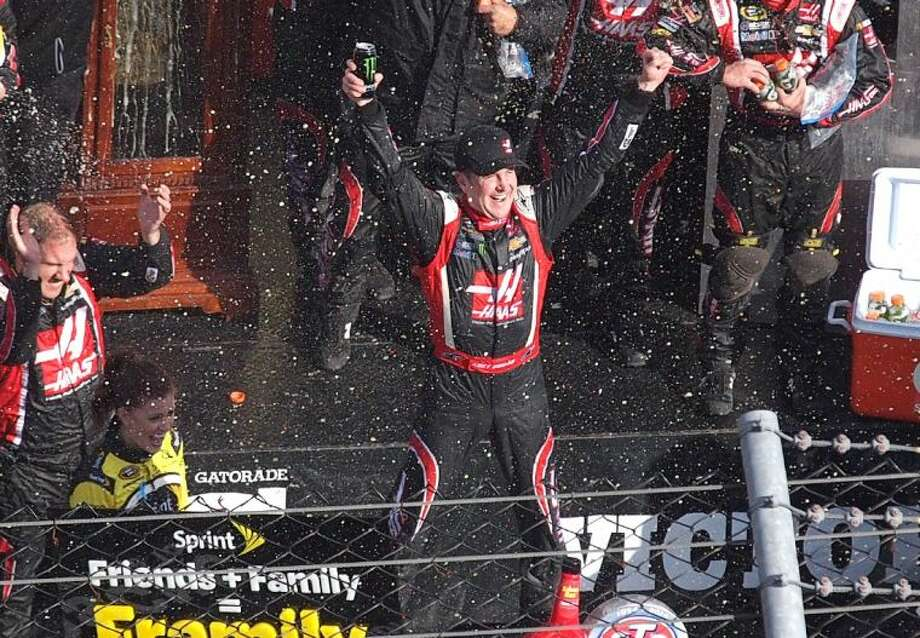 Driver Kurt Busch celebrates in victory lane after winning a NASCAR Sprint Cup auto race at Martinsville Speedway.