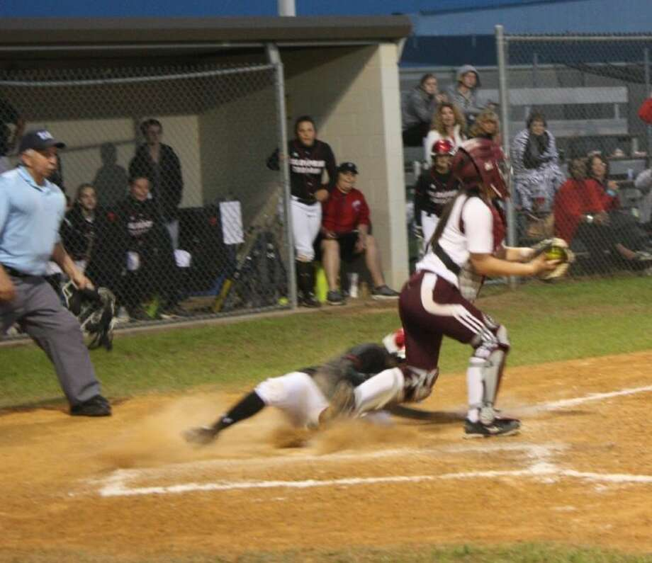 Lady Trojan Jeanette Kelley (5) slides to home plate before LadyHorn Natalie Burns (12) is able to tag her in time. Photo: JACOB MCADAMS
