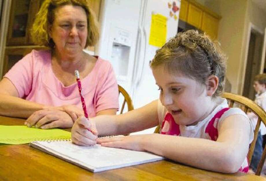Conroe ISD teacher Cindy Johnston helps Maddie Lawrence, a second-grader who is battling cancer, practice writing new vocabulary words Friday at the Lawrence home in The Woodlands. Lawrence leaves Monday on a Make-A-Wish trip to Disney World. Photo: Staff Photo By Ana Ramirez / The Conroe Courier/ The Woodland