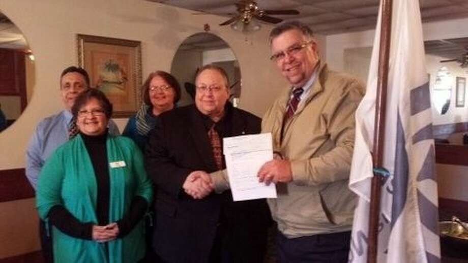 John Switzer, CEO of Pasadena Health Clinic, and staff present John Schneider, President of the Pasadena Noon Optimist, a check for the 13th Annual POJO Tournament.