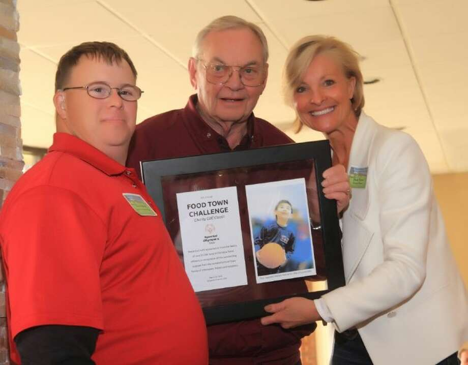 Pictured, left to right: Special Olympics Texas athlete Kevin Harrell presents a Special Olympics Texas award to Ross Lewis, president of Food Town, while Dana Tyson of the Sunny 99.1 FM Morning Show looks on.