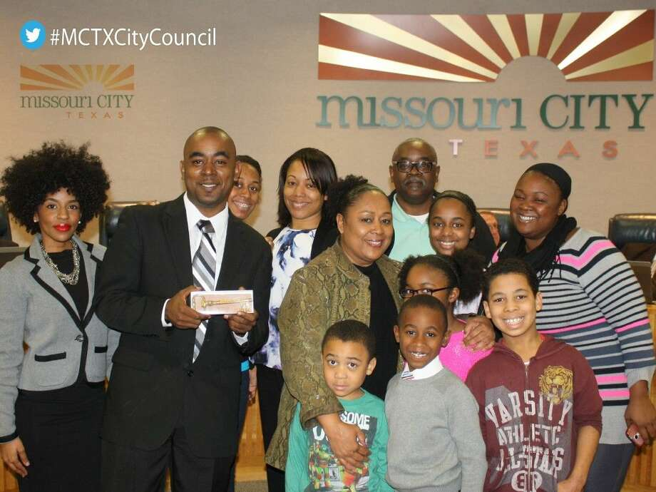 """Johnnie """"John John"""" Moutra III, second from the left, poses with his family and holds his Key to the City."""