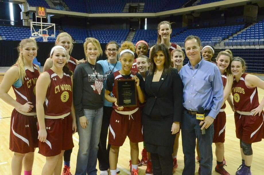 Todd Freed, sports director at KUBE Ch. 57, and Michelle Droubi, senior vice president of Allegiance Bank Texas, present Head Coach Virginia Flores and the Cypress Woods girls' basketball team with the Allegiance Bank Texas Team of the Week trophy on March 4
