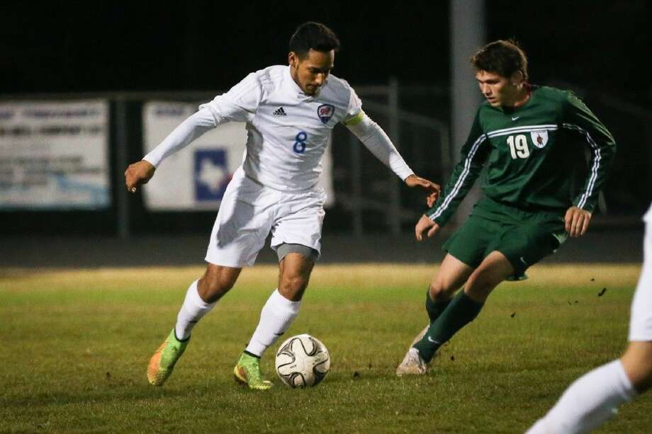 Oak Ridge's Marcos Chavez (8) tries to get past The Woodlands' Liam Smyth (19) during the high school boys soccer game on Friday at Oak Ridge High School.