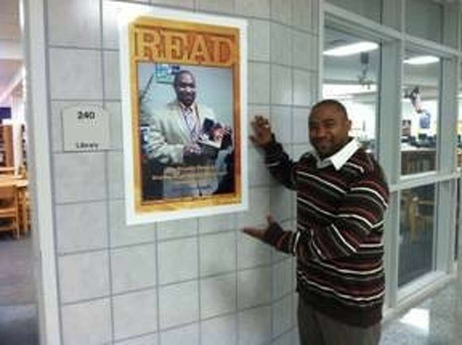 """Dayton High School principal Travis Young stands next to the READ poster that features him. DHS celebrated World Read Aloud Day on March 5. Librarian Dani Nations began the day by reading a passage from """"Wonder"""" by R. J Palacio to the entire school during morning announcements. Photo: Submitted Photo"""