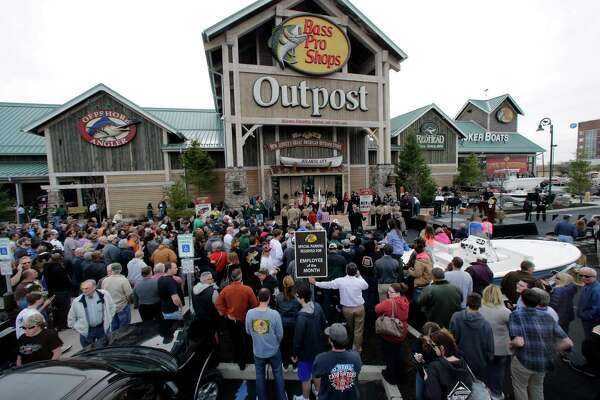 FILE - In this Wednesday, April 15, 2015, file photo, a large crowd of people line up as they wait for the grand opening of Bass Pro Shops Outpost store in Atlantic City, N.J. Outdoor gear giants Bass Pro and Cabela's will combine in a $4.5 billion deal announced Monday, Oct. 3, 2016. (AP Photo/Mel Evans, File) ORG XMIT: NYBZ105
