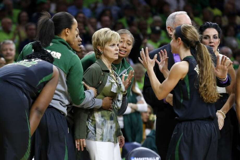 Baylor coach Kim Mulkey has an anxious moment on the bench as she is held back by her players, including guard Makenzie Robertson, right. Notre Dame defeated Baylor 88-69.