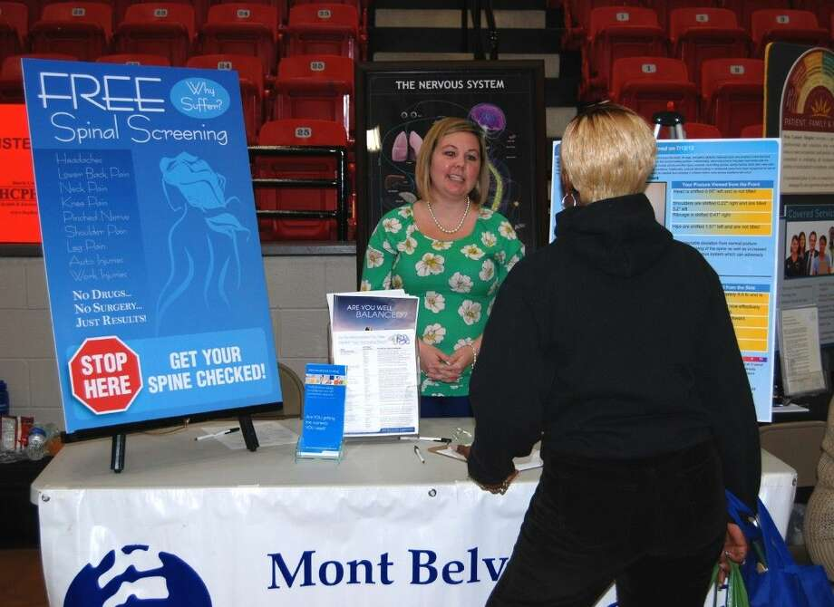 Ashley Taylor of Mont Belvieu Chiropractic Center explains the spinal screening procedure to an attendee at the sixth annual Lee College Health Fair, held in 2014 at the Sports Arena on campus. This year's Health Fair is set for Tuesday, March 24, and will feature 50 local vendors offering free health screenings and information about how to improve overall wellness. Photo: Submitted