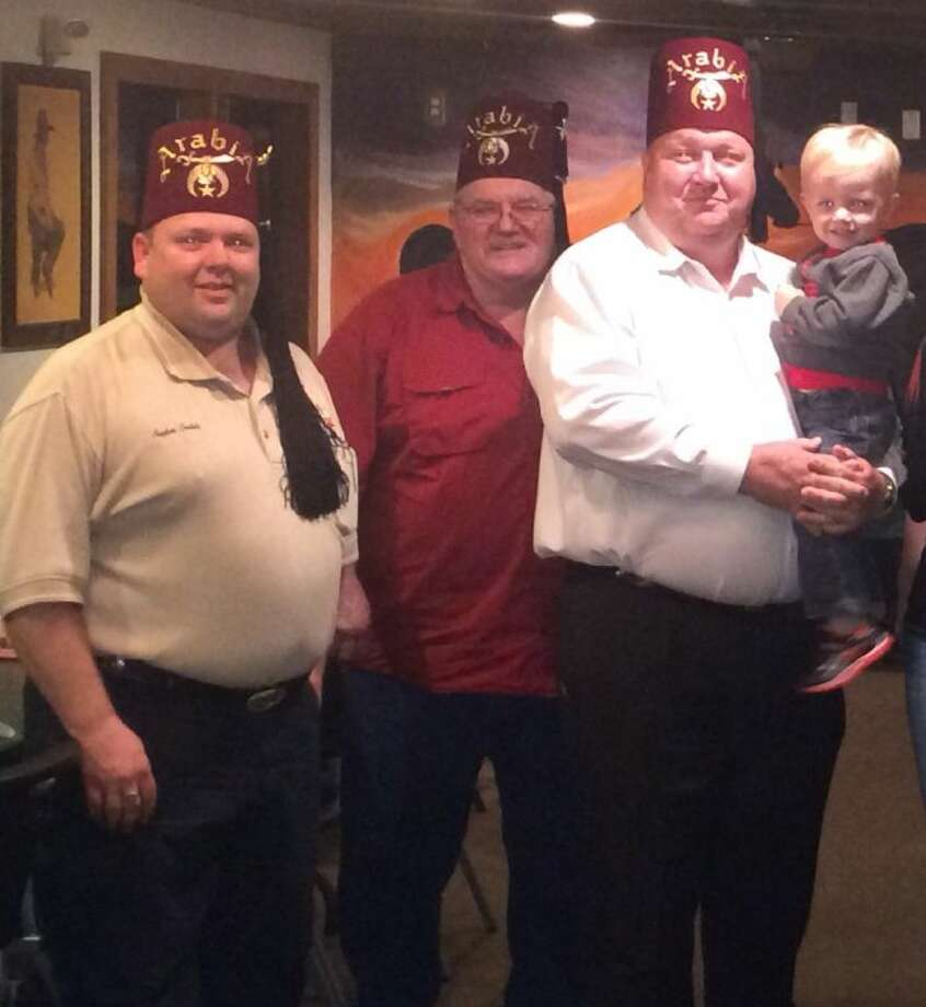 From left, New Caney Shrine Club Vice President Stephen Carlisle, Secretary James Weaver and President Jim Clark holding James Melton, who was recently selected as the club's representative with the Shriners Hospital for Children-Houston.