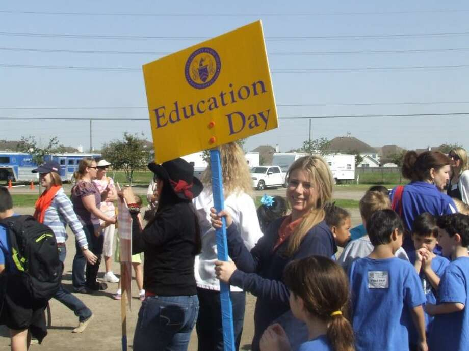 Pin Oak volunteer Jocelyn Davis holds up a sign during Education days at the Great Southwest Equestrian Center in Katy on March 20. More than 300 students from the Katy area participated.