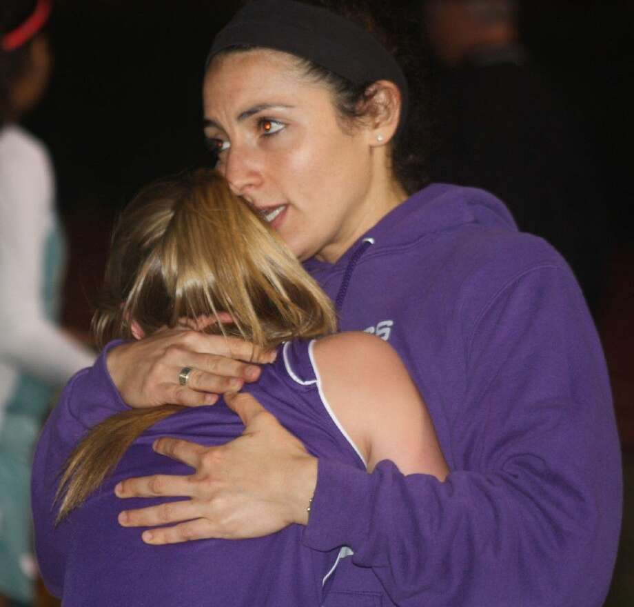 Southmore Intermediate School coach Jordan Land comforts a tearful Jennifer Garza following the seventh-grade 4 by 400 relay race Wednesday night. Southmore finished seventh in 5:18.82. Photo: Robert Avery