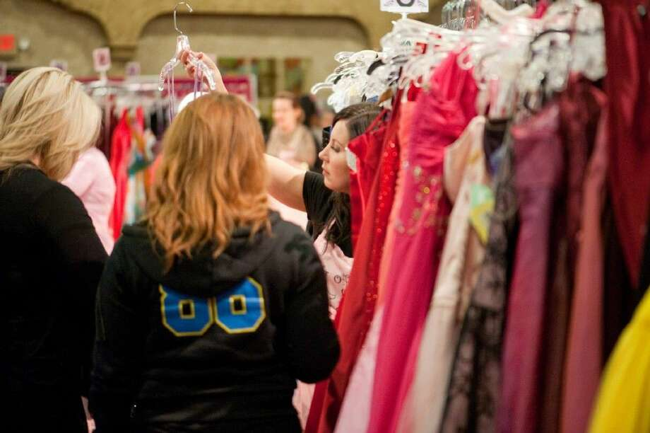 A Giving Gown Foundation volunteer shows a dress. Photo: JULIZZA HOLUB