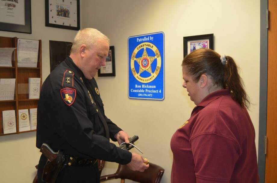 Harris County Constable, Mark Herman, demonstrates how to secure a firearm with a gun lock. Photo: Harris County Constable's Office
