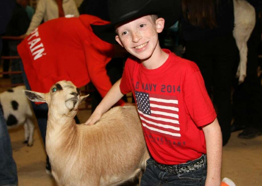 Tomball Intermediate School fifth grader Braeden Buckner enjoyed petting a goat at the Tomball ISD Special Needs Rodeo. Photo: Tomball ISD