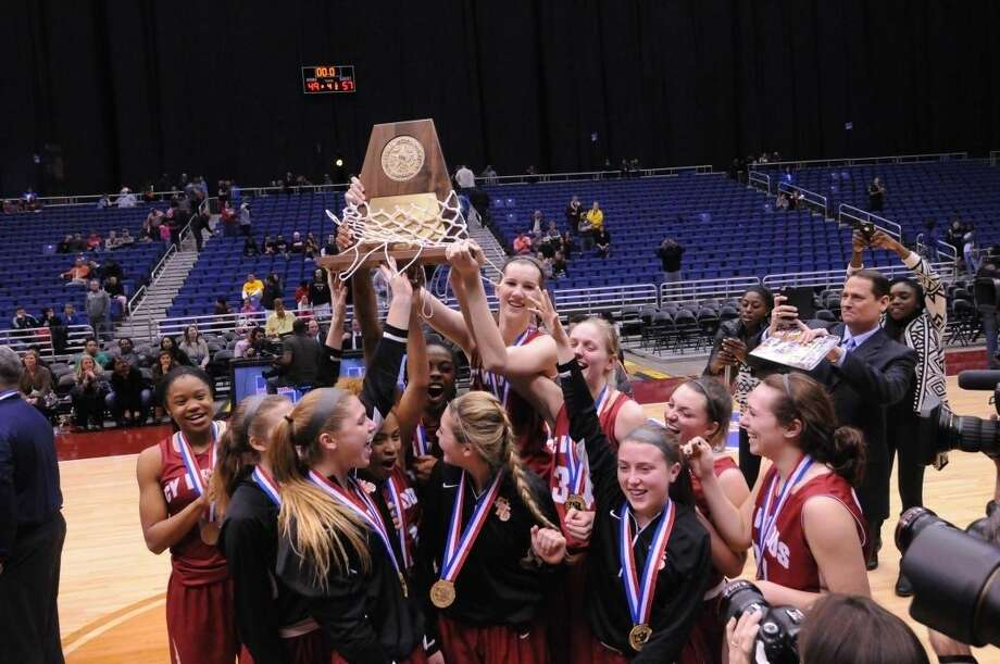 The Cy Woods girls' basketball team hoists the Class 6A state championship trophy after defeating Dallas Skyline, 57-49 Saturday at the Alamodome in San Antonio. Photo: Tony Gaines