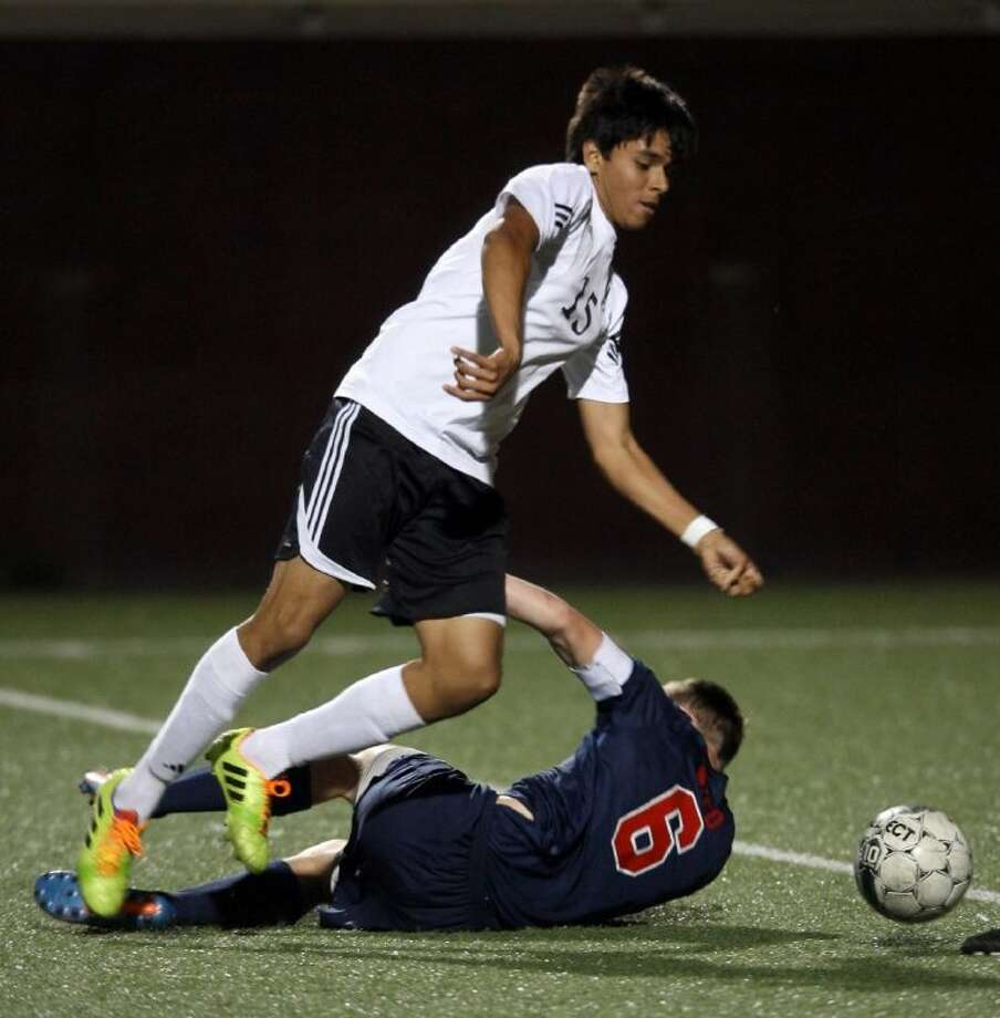 Pasadena's Jose Pacheco runs over Clear Lake's Jason Weed during Friday night's hard-fought Area championship game in Deer Park. Photo: Kar Hlava