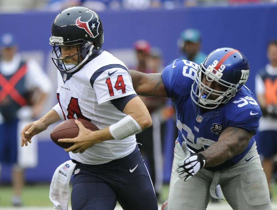 Texans quarterback Ryan Fitzpatrick, left slips out of the pocket under pressure from Giants defensive tackle Cullen Jenkins. The Giants won 30-17. Photo: Bill Kostroun