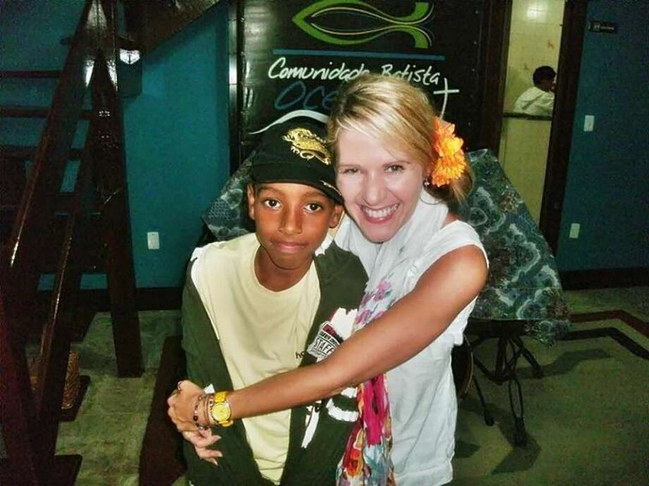 Longtime dance instructor Tonya Thompson poses with a new friend on one of her mission trips.