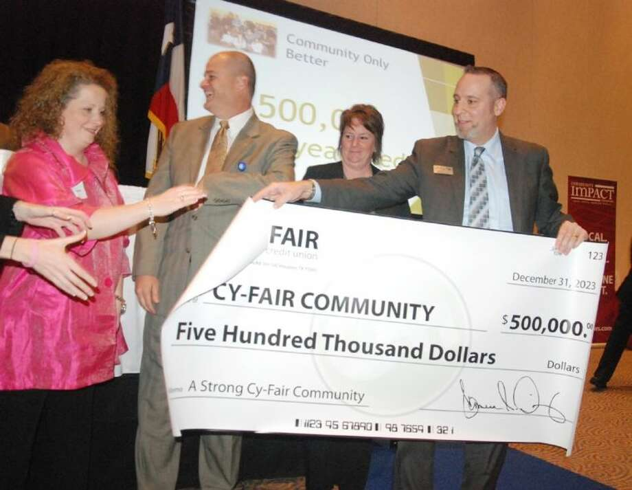 Cy-Fair Federal Credit Union President Cameron Dickey, right, unrolls a $500,000 pledge check to the CFISD community, joined by (L-R) Leslie Martone, Cy-Fair Houston Chamber of Commerce president; Dr. Mark Henry, CFISD superintendent; and Marie Holmes, Cy-Fair Educational Foundation executive director. Photo: Submitted Photo