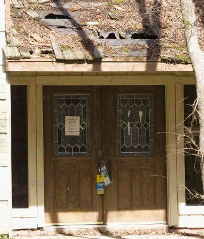 The front door of the abandoned house at 2610 S. Wildwind Circle is locked and bears a sign cautioning trespassers of dangerous conditions.