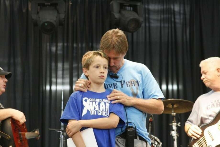 Phil Baumann gives his son, Colby, a hug during a past CureFest.