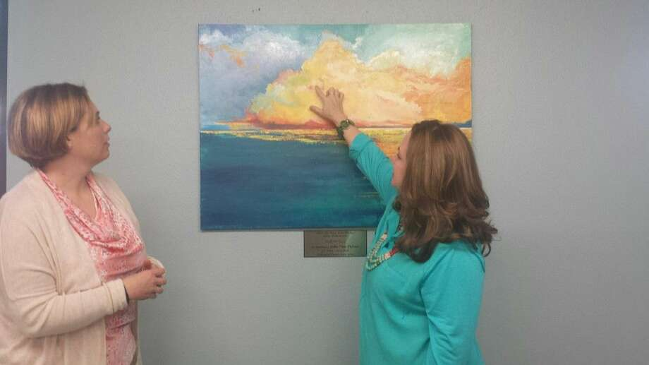 Holly Nowak, right, explains some of the details of her painting to Church of Christ Kingwood Children's Minister Shannon Rains. Nowak painted the painting in memory of Julia Palmer who worked in the nursery for years.
