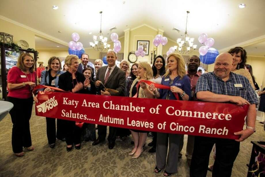 Joseph Jasmon, chief operating officer of The LaSalle Group, cuts the ribbon at the official grand opening of Autumn Leaves of Cinco Ranch. He is joined by Ann Hodge (left), president/CEO of the Katy Area Chamber of Commerce. Photo: Kenzie DelaTorre