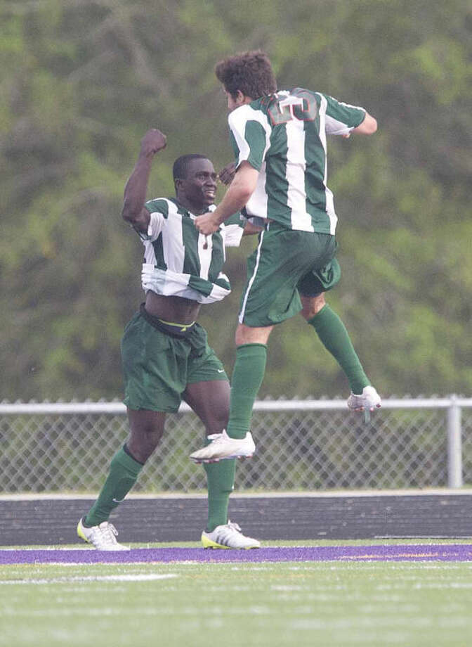 The Woodlands midfielder Bubacarr Jobe (7) celebrates with Orimo Covarrubias (25) after his second period goal during a Region II-5A area playoff game at College Station High School Thursday. The Woodlands defeated Lake Travis 2-0. Photo: Jason Fochtman