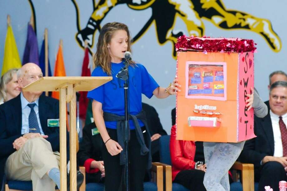 Ed White Elementary student Mackenzie Stewart describes her school project, a Valentine's Day card vending machine, during a ceremony to celebrate Ed White Elementary's fiftieth anniversary Wednesday, Mar. 12.