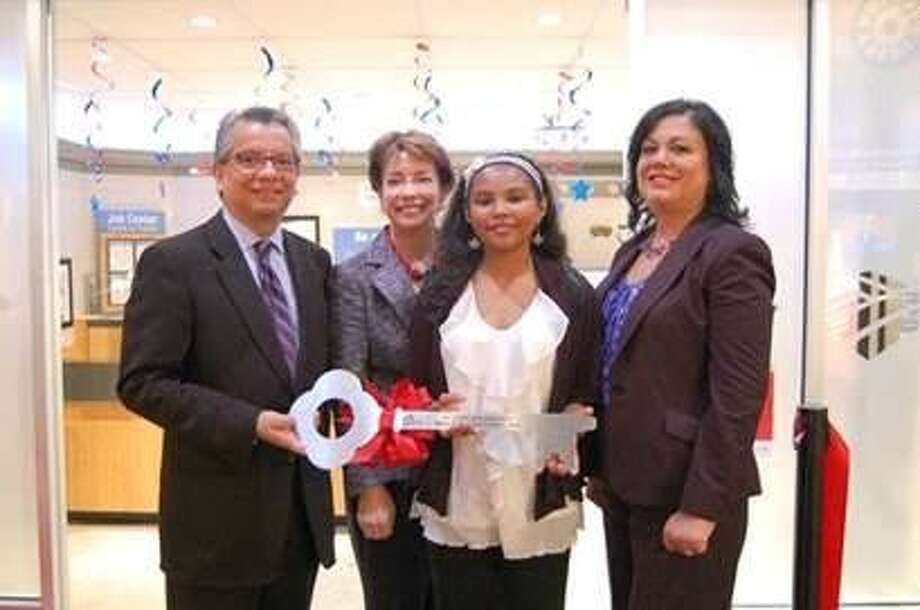 "David Ruiz with Bank of America accepts a key to Kidtropolis from its ""Mayor for a Day"" Alexis Mack, second from right, to celebrate the bank's new branch in the Children's Museum of Houston exhibit. Also participating were museum Executive Director Tammie Khan, second from left, and Patti Abshire with Bank of America."