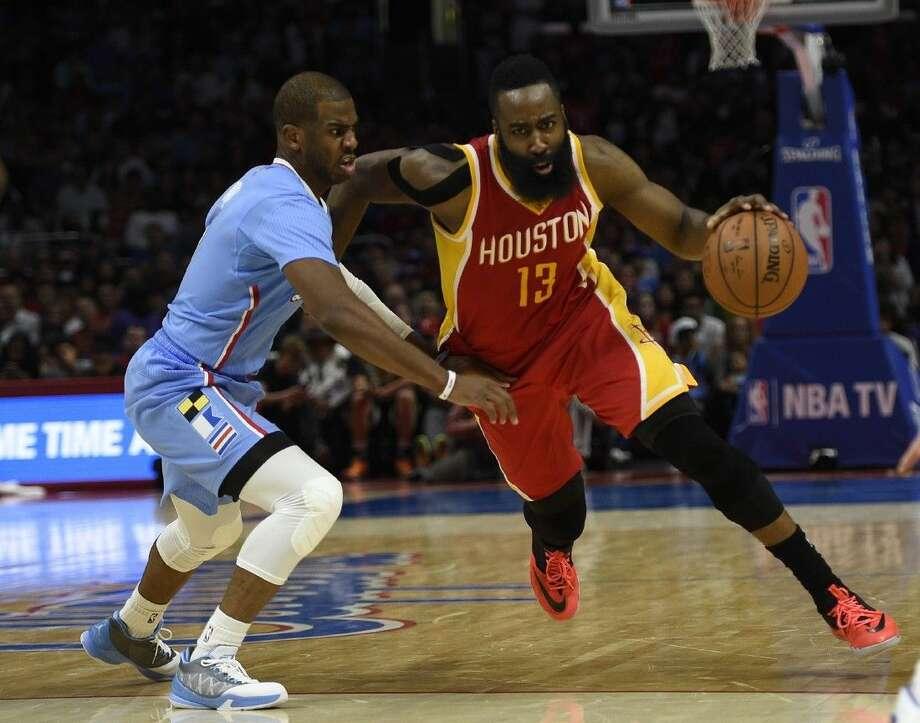 Houston Rockets guard James Harden, right, drives against Clippers guard Chris Pau. The Rockets won 100-98.