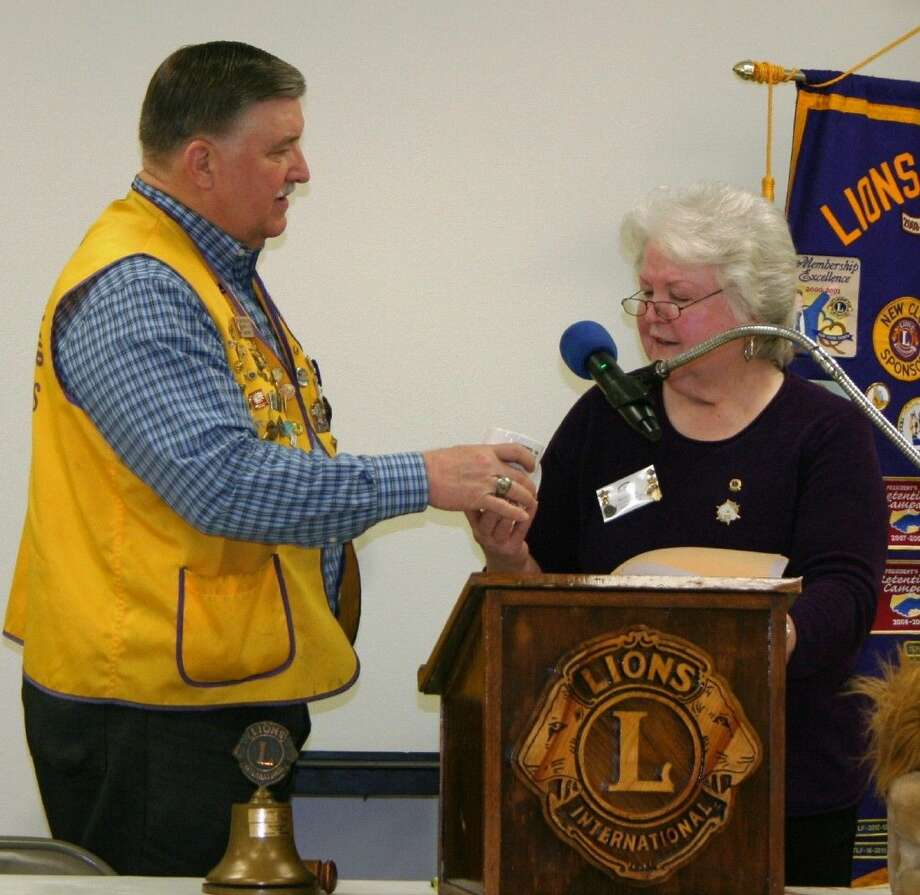 Cleveland Lions Club member Mike Penry presents guest speaker Betty Ezell with a coffee mug during the March 10 meeting. Photo: Stephanie Buckner