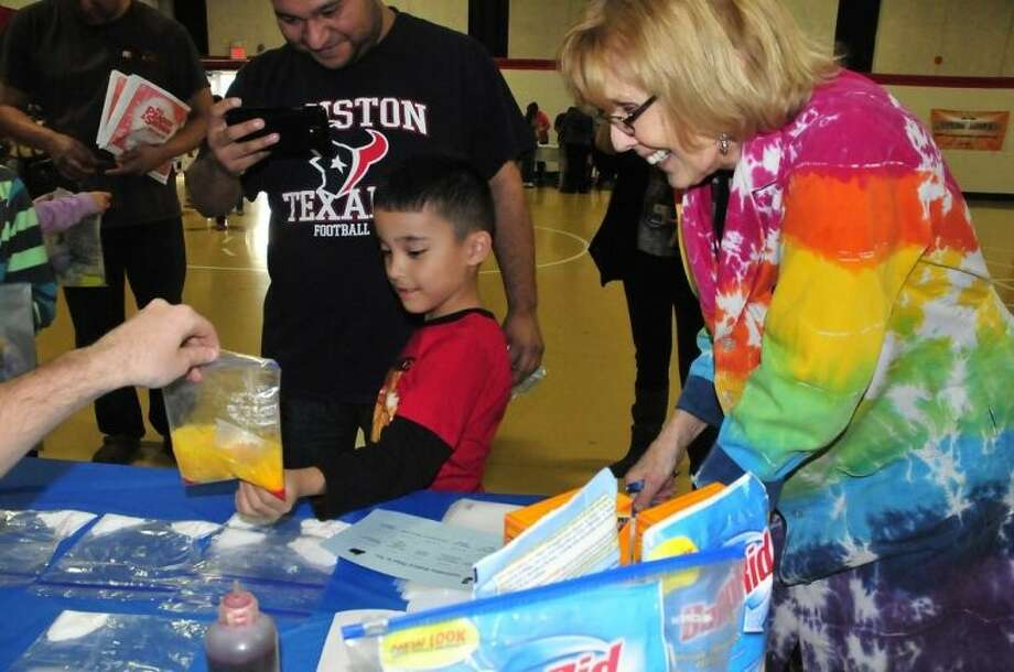 (right to left) Dr. Ann Cartwright, physical science department chair at San Jacinto College, explains the science behind the chemistry in a bag activity to Isaiah Garcia, first-grader at Mae Smythe Elementary, and his father, Luis Garcia. Photo credit: Jeannie Peng-Armao, San Jacinto College marketing, public relations, and government affairs department.