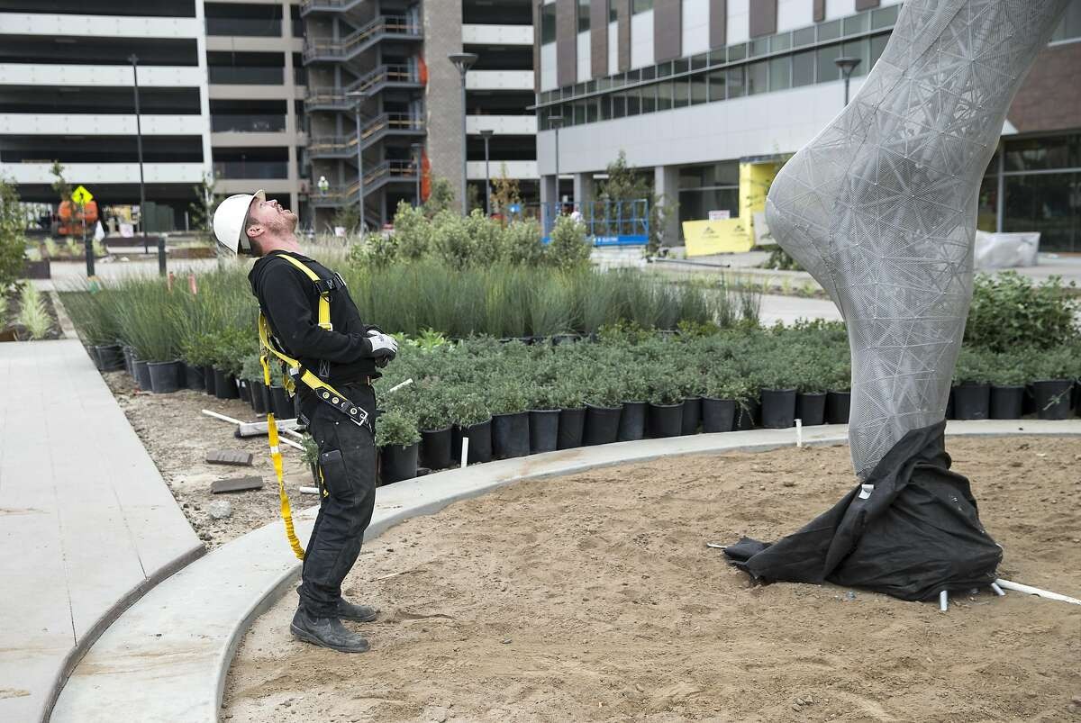 """Artist Marco Cochrane leans up to talk with his crew during the final installation of his sculpture """"Truth is Beauty"""" at the new San Leandro Tech Campus where it is now permanently installed in San Leandro, Calif., on Monday, October 3, 2016. The sculpture was originally shown in it's final form at Burning Man in 2013 and is the second in a series of three sculptures known collectively as The Bliss Project."""