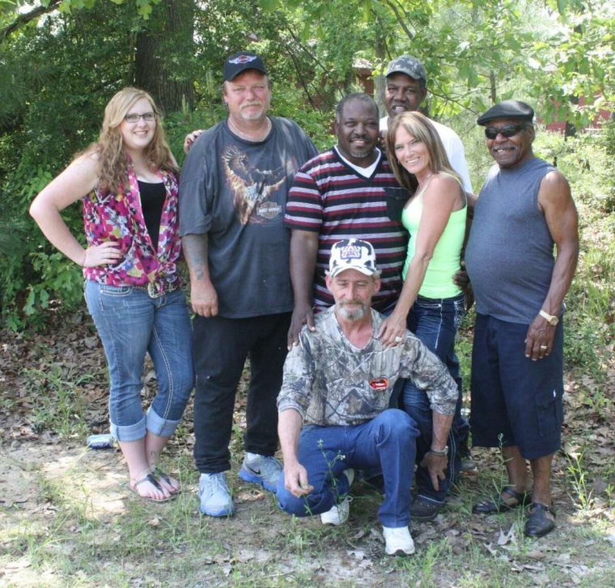 """The Coopers stand here not with friends but with family in bond and love. Pictured are (back row) Nathaniel Cooper, (middle row, left to right) Allison Jeffers, Dan Dempsey, Wayne Cooper Vanessa Black, Roosevelt Cooper; and (front row) Larry """"Bubba"""" Craven."""