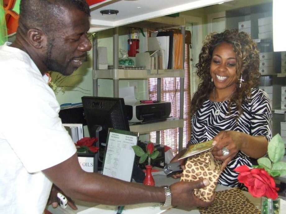 Grayce Egami helps a customer at her boutiqe located at 105 Pine Street in Tomball. The boutique sells Egami's own Divine's Serum, which she created to help heal her daughter's severe eczema.