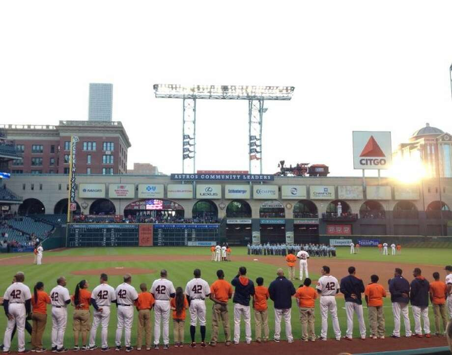 Astros stand shoulder to shoulder with members of the Astros Urban Youth Academy during the singing of the national anthem. The special game was a celebration of Jackie Robinson Night.