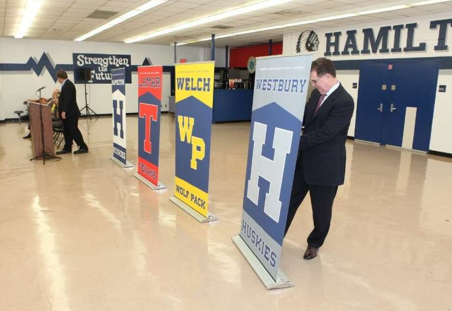 Houston ISD Superintendent Dr. Terry Grier turns adjusts a banner showing one of the new mascot names announced April 15 during a press conference at Hamilton Middle School. The new mascots comply with a change in district policy and replace symbols considered by some as culturally insensitive. Photo: Alan Warren