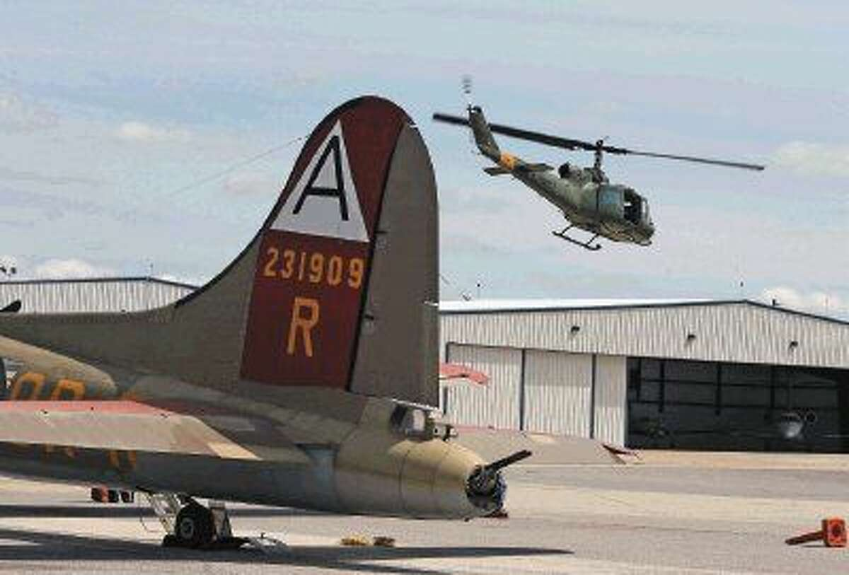The Bell UH-1E Iroquois flies past the B-17 taking visitors on a flight.
