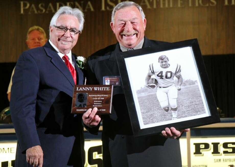 Inductee Lanny White (right), an all-state halfback for the Pasadena Eagles in 1967, receives his plaque and portrait from Hall of Fame President Terry Brotherton. Photo: Courtesy Pasadena ISD