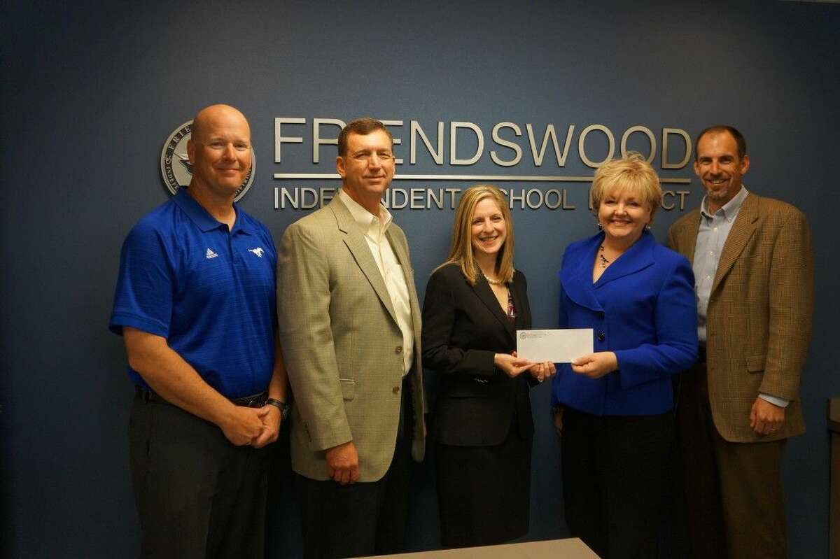 Kenny and Kristi Koncaba of Texan Bank present a $100,000 check to Friendswood ISD to become the Premier Sponsor for the new digital stadium sign to be launched for the Fall 2015 Friendswood High School Football season. Superintendent Trish Hanks accepts the check and is joined by Deputy Superintendent Thad Roher (far right) and Athletic Director Robert Koopmann. Celebrating its fourth anniversary, Texan Bank in Friendswood is one of four in the Greater Houston area.