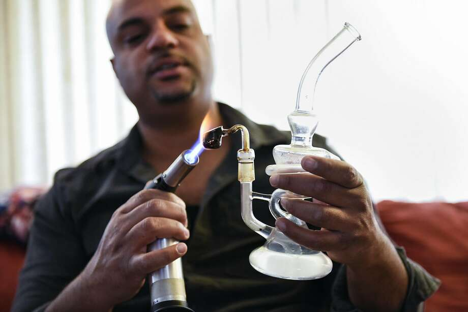 Cannabis entrepreneur Terryn Buxton heats a pipe for smoking cannabis extract at his Oakland home. Photo: Michael Short, Special To The Chronicle