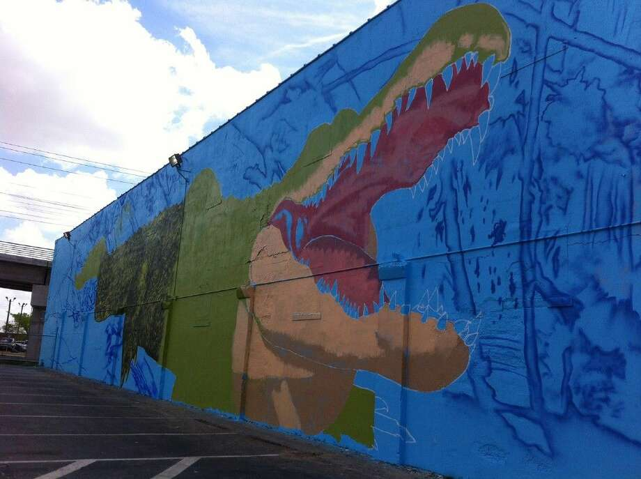 "French artist Sebastian ""Mr. D"" Boileau of Eyeful Art Murals and Designs is creating a building-size mural of the University of Houston-Downtown (UHD) mascot - Ed-U-Gator - on the north side of a storage facility on campus. He also is painting the UHD logo and tagline, ""Major Opportunity,"" on the south side of the building, which faces I-10."