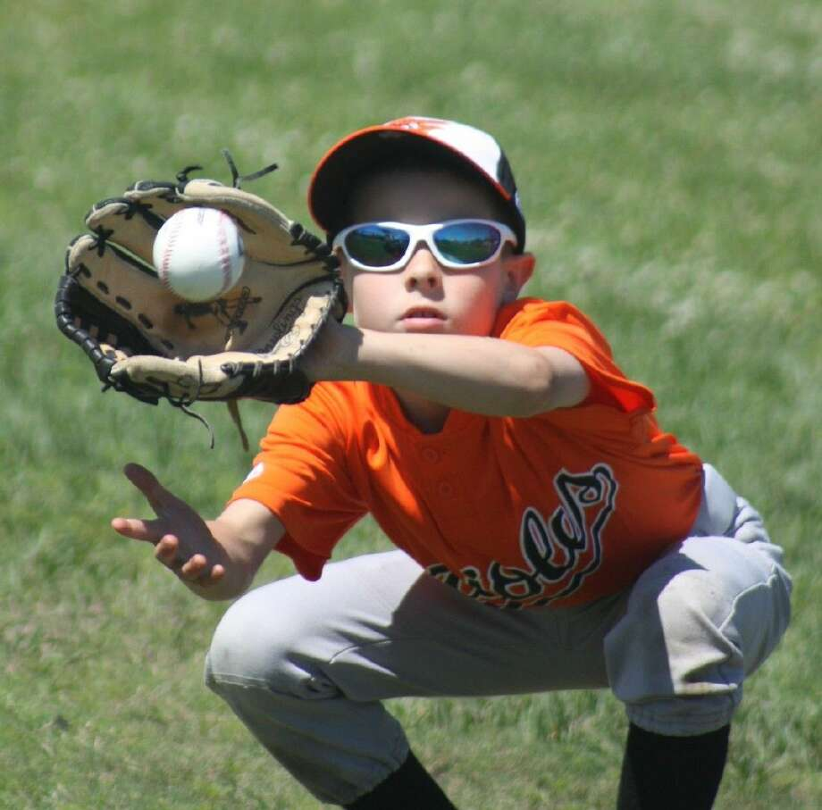 D.J. Nicastro of the Orioles concentrates on catching a low throw by a teammate prior to the Orioles taking the field for their season opener Saturday, just one of many contests during the sun-splashed day for the historic debut of Deer ParkBaseball Pony League. Photo: Robert Avery