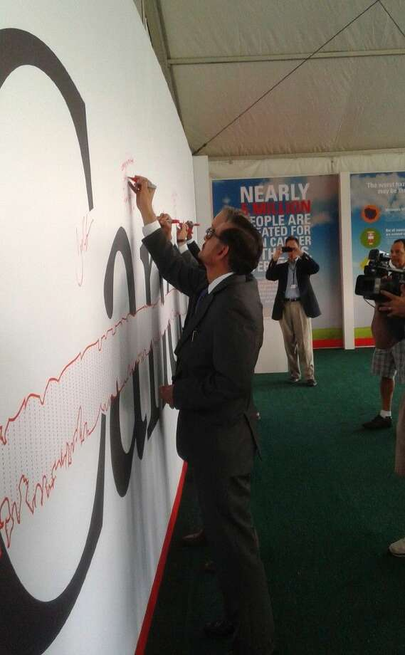 "Shell Oil Company's global health lead Dr. Faiyaz Bhojani signs M.D. Anderson's ""slash through cancer"" wall at the Houston Shell Open."