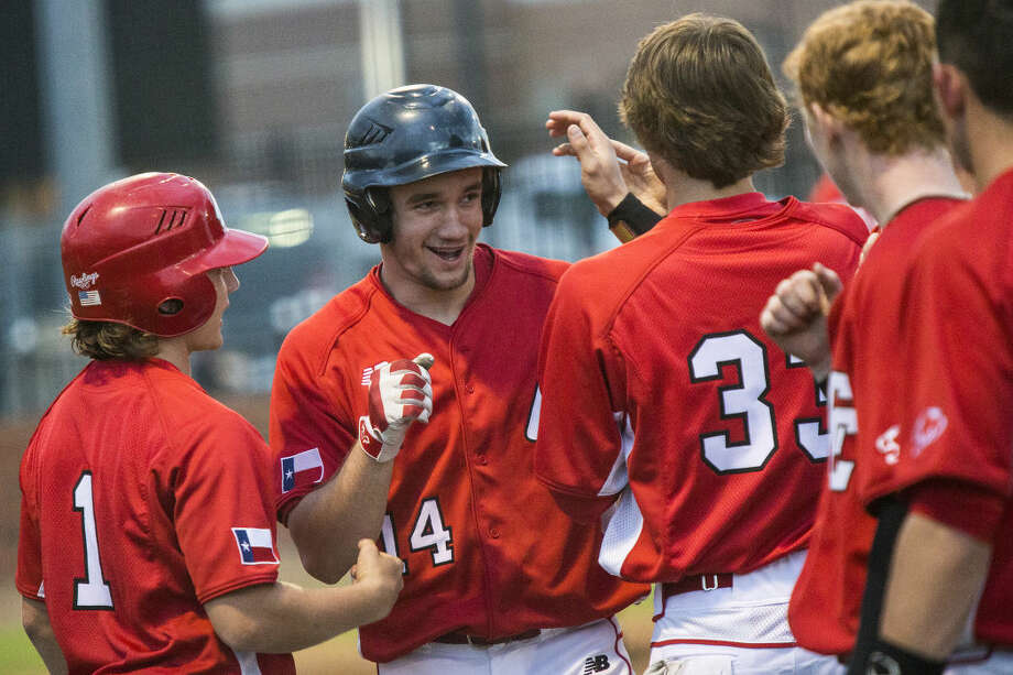 Crosby's Alec Lewis (14) celebrates with teammates after hitting his first of two walk-off home runs during Crosby's 9-8 extra inning victory over Humble on March 18, 2015, at Humble High School. Photo: ANDREW BUCKLEY