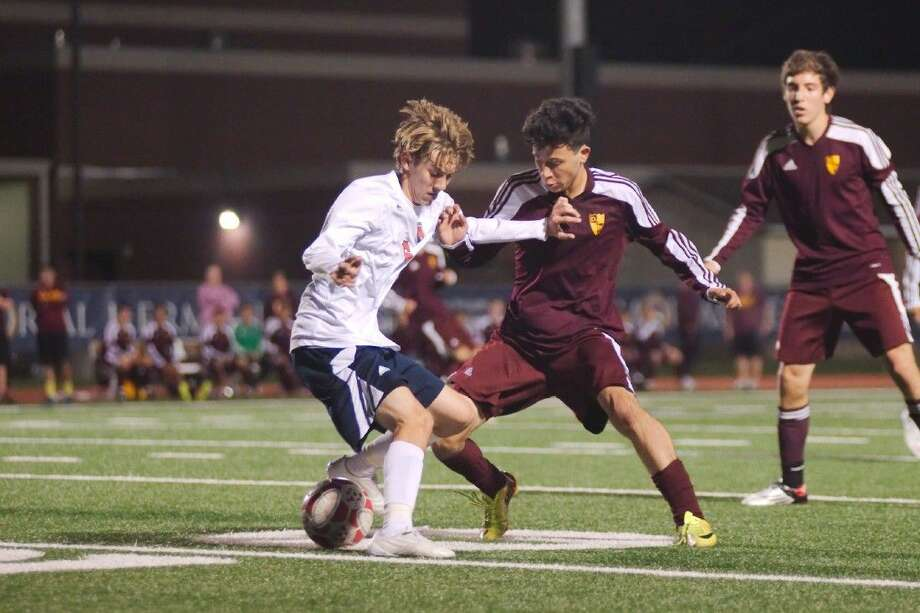 A Deer Park and a Pearland Dawson player battle for control of the ball during Deer Park's 3-0 bi-district championship win in the boys division. Photo: Kirk Sides