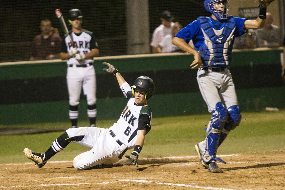 Zak Keller (6) slides into home for the final run of Kingwood Park's 13-3 victory over C.E. King on March 31, 2015, at Kingwood Park High School.