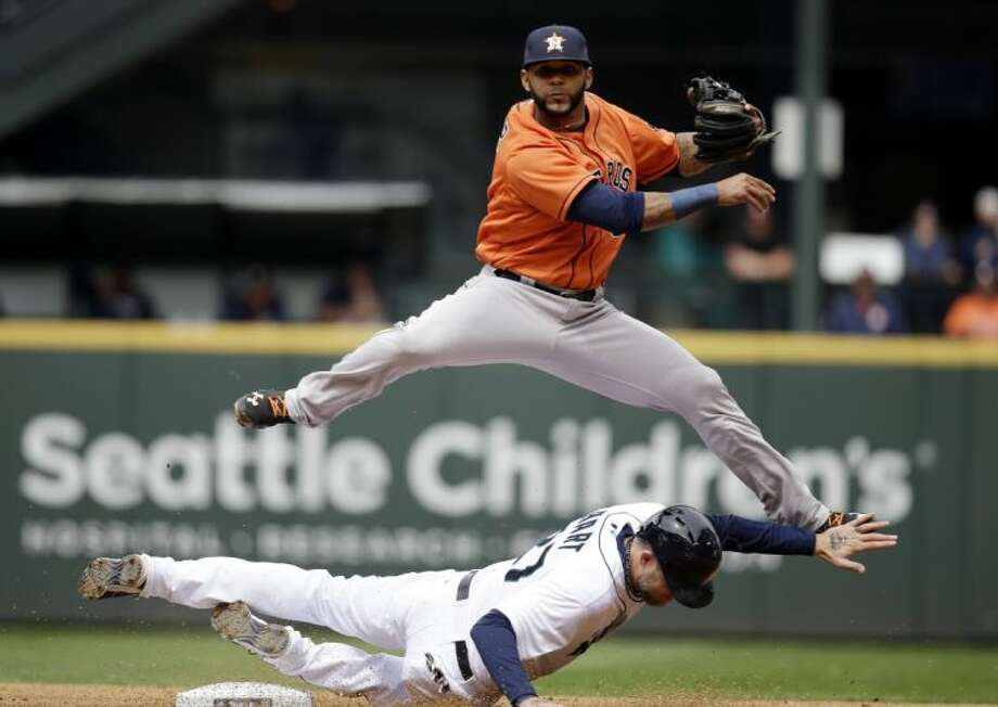 Houston Astros shortstop Jonathan Villar leaps out of the way after forcing out Seattle Mariners' Corey Hart at second base and throwing the ball to first in the fourth inning of a baseball game Wednesday, April 23, 2014, in Seattle. Hart and Justin Smoak were out on the inning-ending double play.